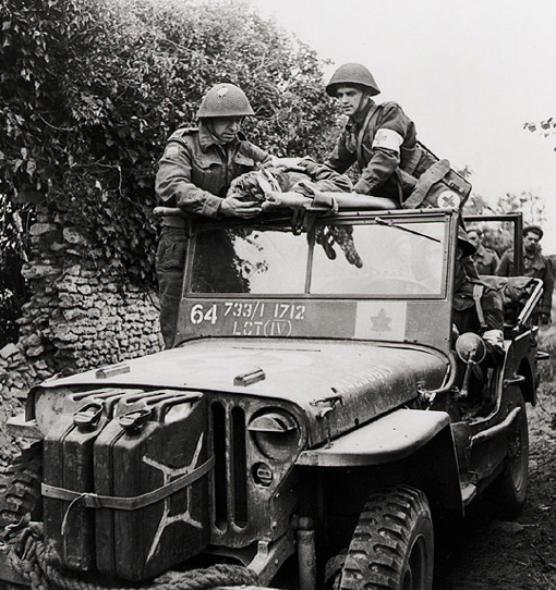 A wounded man of the 3rd Canadian Infantry Division is evacuated by members of the Regimental Aid Post, with help from the regiment's Padre, near Caen, Normandy, 15 July 1944.