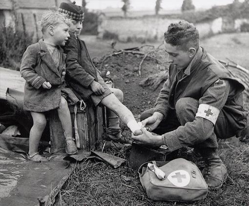 Le caporal W.J. Curtis du Corps médical militaire royal du Canada soigne la jambe brûlée d'un jeune garçon français, sous les regards de son frère cadet. Entre Colomby-sur-Thaon et Villons-les-Buissons, Normandie, 19 juin 1944.