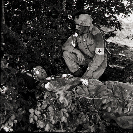 Captain A.W. Hardy, Medical Officer with the West Nova Scotia Regiment, lying wounded in a copse, shot through the foot by Italian paratrooper while treating a wounded West Nova Scotian, with Private W.E. Dexter, WNSR, a stretcher-bearer who was wounded in the head. Near Santa Christina, Italy, September 1943.