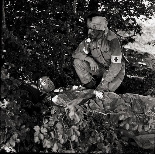 Le capitaine A.W. Hardy, médecin militaire avec le Régiment West Nova Scotia Regiment, est étendu blessé dans un bosquet. Il a été atteint au pied par un parachutiste italien alors qu'il soignait un blessé de son régiment, en compagnie du soldat W.E. Dexter, WNSR, un brancardier blessé à la tête. Près de Santa Christina, Italie, septembre 1943.