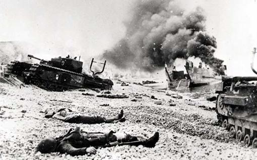 Des cadavres jonchent la plage près de deux chars Churchill du 14e Régiment blindé (Calgary), enlisés dans les galets. Derrière, une épaisse fumée s'échappe du LCT 5.