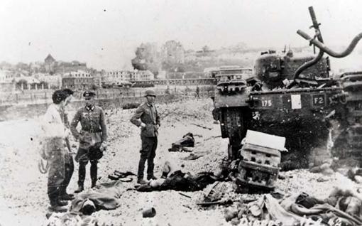 Après la bataille, un officier et des soldats examinent un des chars Churchill immobilisé sur la plage devant la Promenade, sa chenille gauche brisée. Des blessés étendus au sol sont sur le point d'être emmenés. Dieppe, 19 août 1942.