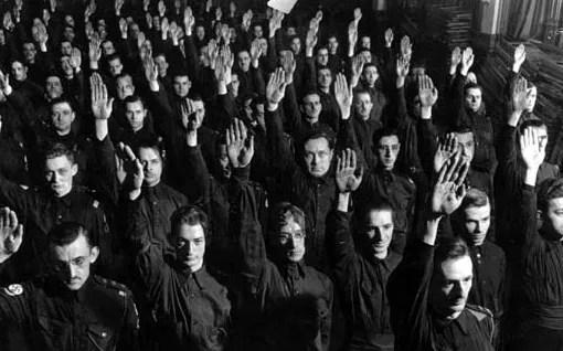 Arborant fièrement l'uniforme du Parti de l'union nationale, des partisans saluent lors d'une réunion à Montréal, en 1939.