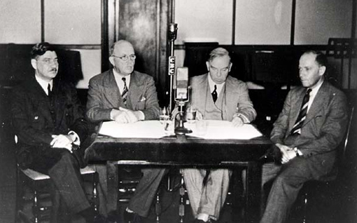 On September 3, 1939, Prime Minister W.L. Mackenzie King (right of microphone) and Minister of Justice Ernest Lapointe (left) speak to the nation on the CBC radio network, King in English and Lapointe in French.