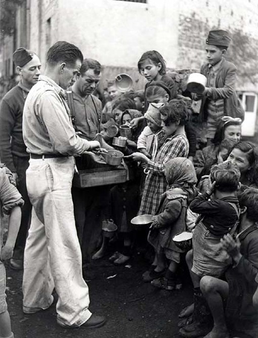 Italian civilians suffered from injuries caused by mines, shells and stray bullets. Many lost their homes and crops. Here gunners Chink Gades and Johnny Scott, 11th Field Regiment, serving corned beef to children in Acireale, December 13th, 1943.