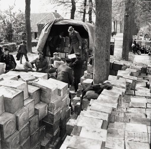 Des civils hollandais chargent de nourriture un camion fourni par les Canadiens, à la suite d'un accord entre les Allemands, les Hollandais et les Alliés, pour permettre la distribution de nourriture à la population hollandaise. Près de Wageningen, Pays-Bas, 3 mai 1945.