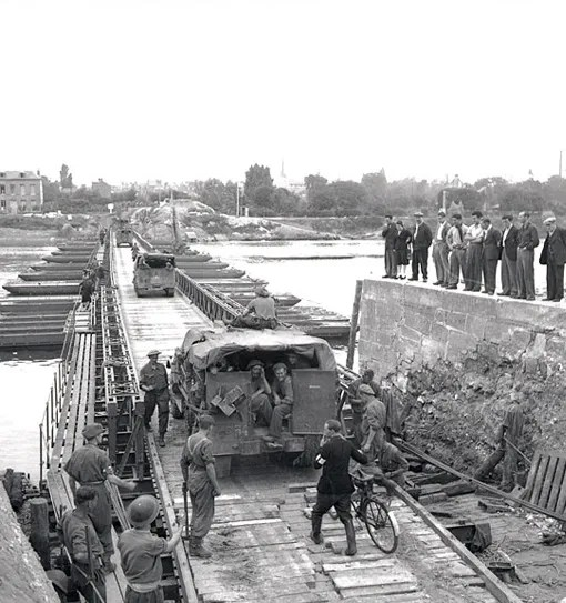 Vehicles of the 4th Canadian Armoured Division crossing pontoon bridge over the Seine River near Elbeuf, France, August 28th, 1944.