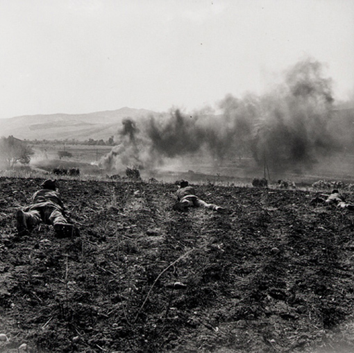Men of the Princess Patricia's Canadian Light Infantry fighting on a ridge near Valguarnera. In the distance, enemy vehicles are burning.