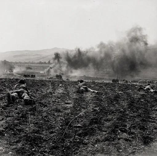 Des hommes du Princess Patricia's Canadian Light Infantry combattent sur une crête voisine de Valguarnera. On aperçoit au loin des camions ennemis en flamme.