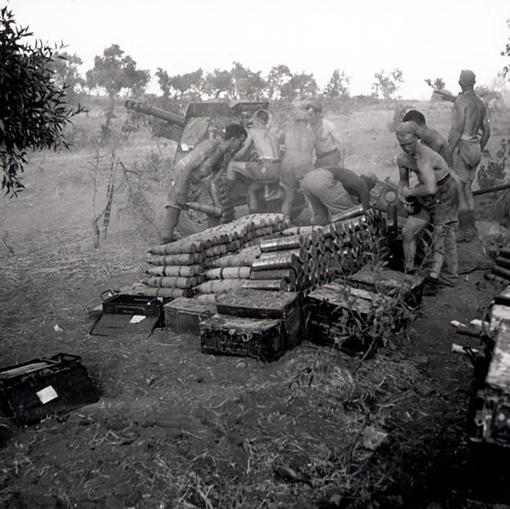Sous la chaleur et la poussière, les artilleurs de la 7e Batterie, 2e Régiment de campagne, font feu sur les positions ennemies au moyen un canon de 25 livres. Nissoria, 28 juillet 1943.