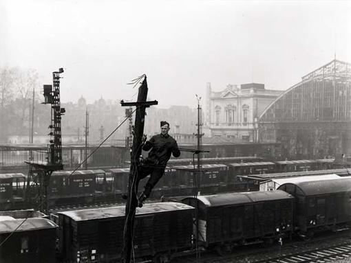 Le signaleur J. Bennett de la 1re Compagnie de télégraphistes pose des fils sur les poteaux de la gare de chemins de fer de Louvain en Belgique, le 6 janvier 1945.