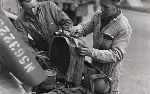 Deux mécaniciens du Corps royal canadien de génie électrique et mécanique, L.A. Einarson de Lundar au Manitoba et Richard Donovan de Limoilou, Québec, replacent le radiateur d'une jeep après avoir remis le moteur en état.
