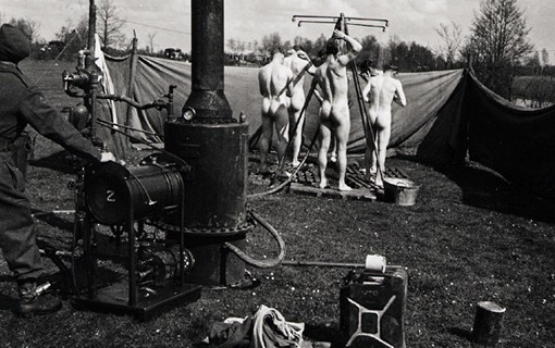 Le long de l'axe de l'avancée canadienne, à la limite avec le front fluide des blindés, une douche portative est installée. Alimentée par un petit ruisseau qui coule à proximité et par un peu d'essence pour faire fonctionner le chauffe-eau, elle permet à beaucoup de prendre un premier bain chaud depuis qu'a commencée la poussée au-delà du Rhin, Wouenhaus, 8 avril 1945.