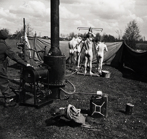 Alongside division axis of advance just behind the fluid armoured front, mobile bath is set up. A small stream nearby and enough gasoline to run water heater and many have the chance of the first bath since the beginning of the push across the Rhine. Wouenhaus, 8 April 1945.