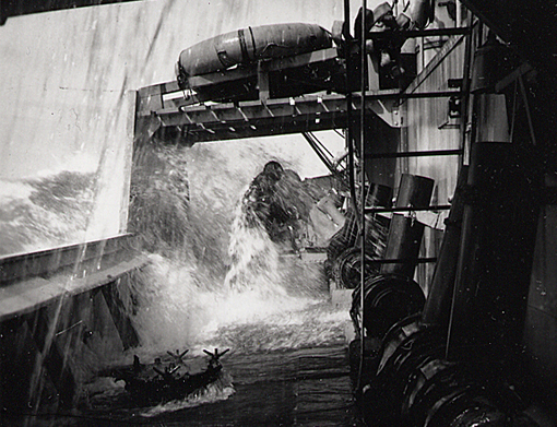 A sheet of sea water splashes over a crew member on HMCS Trillium, September 1943.