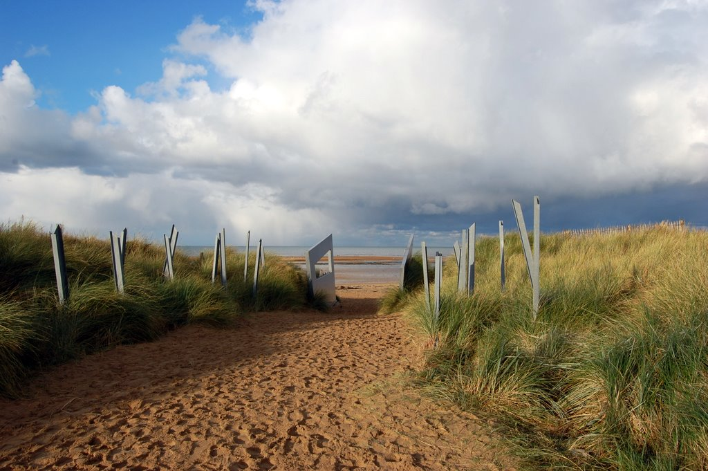 Colour photo. Metal spikes and walls line a well-trodden path towards Juno Beach.
