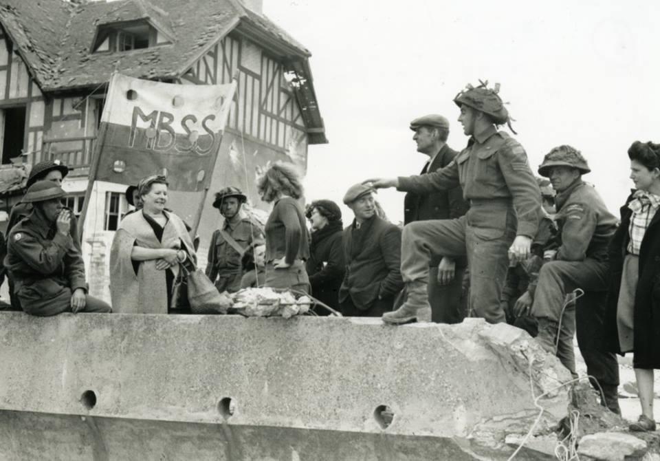 Black and white photograph.  Infantrymen of Le Régiment de la Chaudière talking with French civilians, Bernières-sur-Mer, France, 6 June 1944. Source: Lieut. Frank L. Dubervill / Canada. Dept. of National Defence / Library and Archives Canada / PA-132463 / Courtesy of the Juno Beach Centre Association