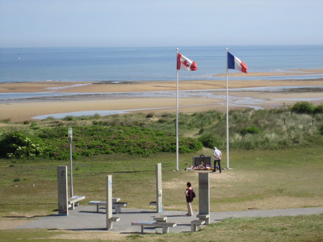 Colour photo. A view of Juno Park, the beach, and a small memorial