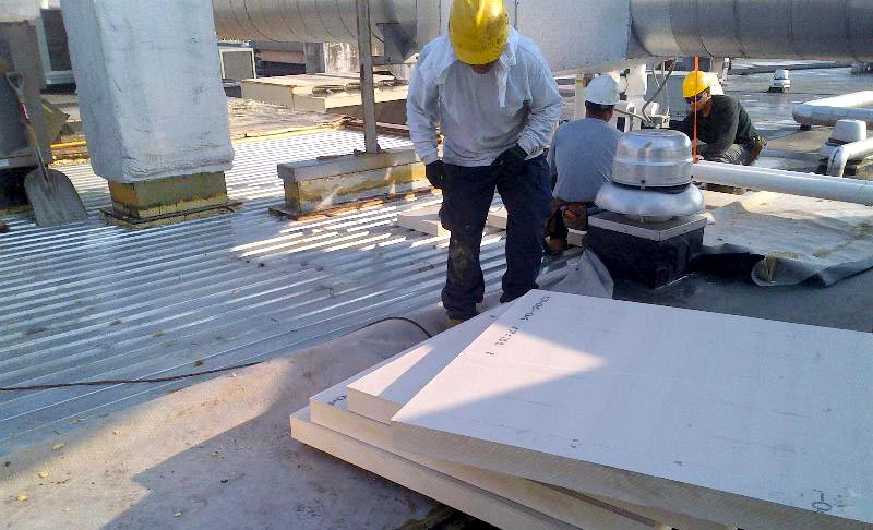 Polyisocyanurate insulation being installed on a commercial roof