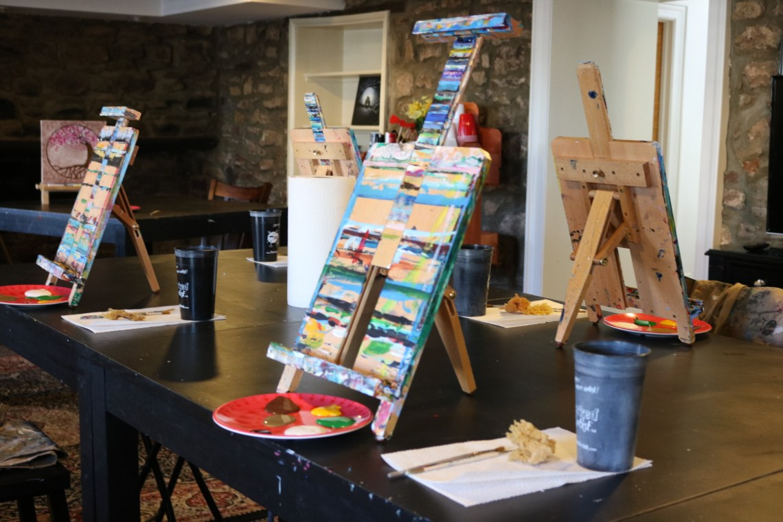 photo of easels, plates with pain, paint brushes and a cup of water on a table