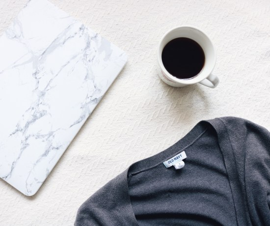 flat lay of my macbook, a cup of black coffee, and a grey cardigan