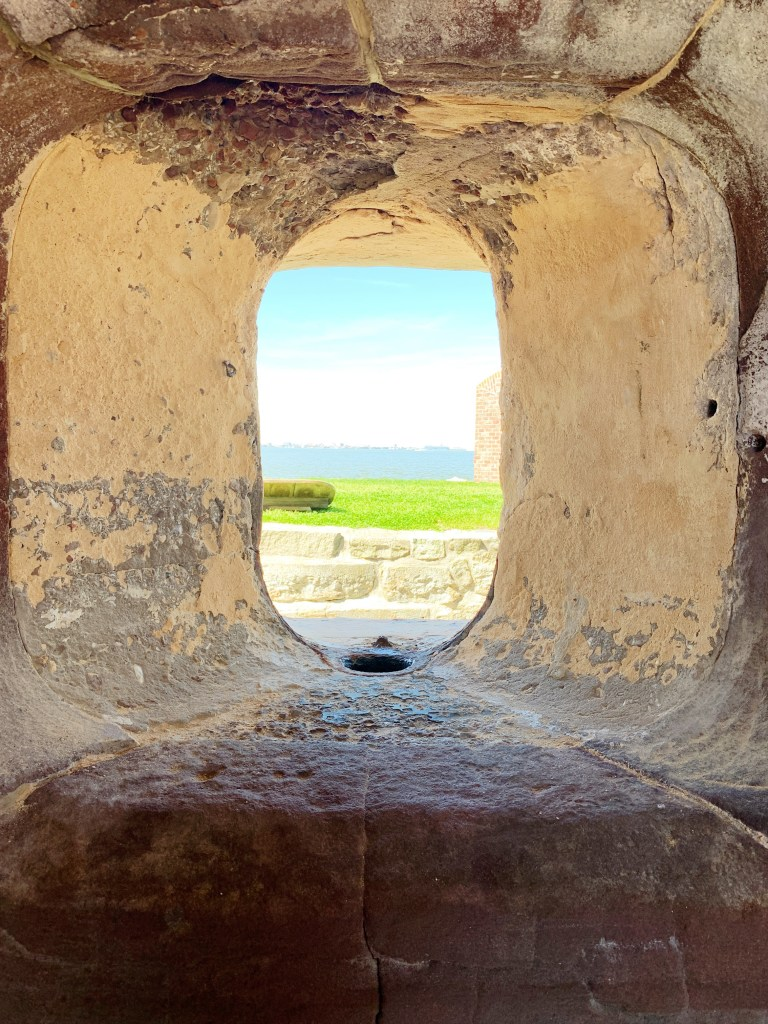 a photo of the vantage point of looking through one of the port holes that a canon would shoot out of. Through the port hole is grass and then the body of water.