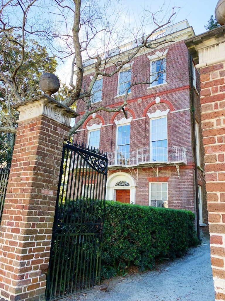 a photo of the Nathaniel Russel House in Charleston which is three stories and with a brick front face. There are three windows on each level and the second level included balconies