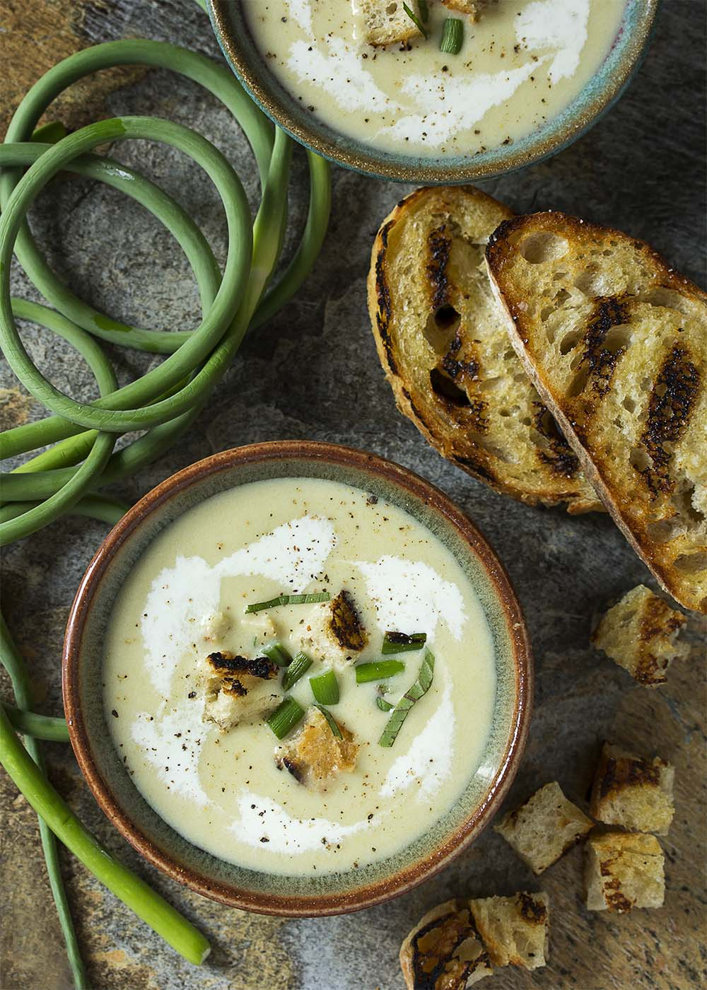 Top view of bowls of garlic scape soup garnished with grilled bread crumbs, basil, and swirls of cream.