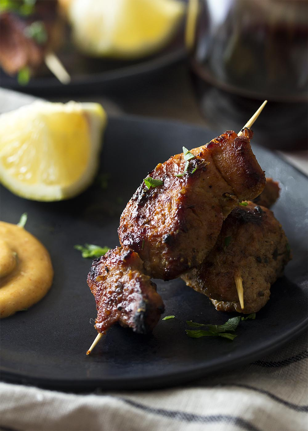 Close up of two skewers of pinchos morunos on a small black plate. Wedge of lemon and dollop of aioli in the background.