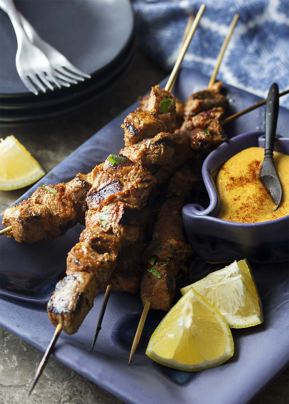 Long skewers of pinchos morunos on a blue serving platter with wedges of lemon and a bowl of aioli.