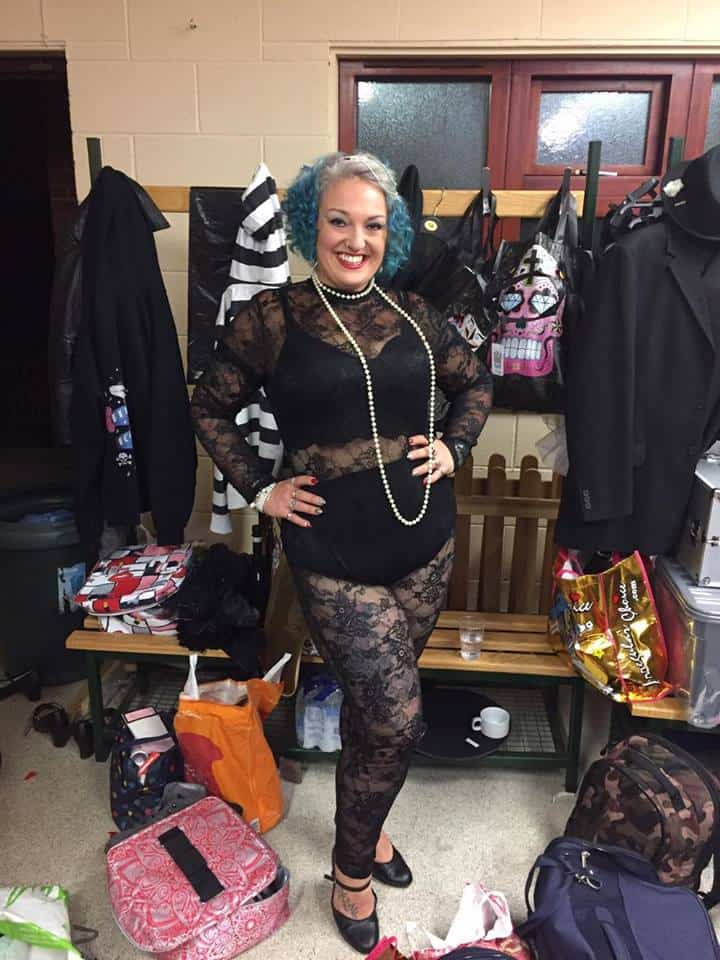 Lady with blue heair and raunchy outfit made from black lace smiling in a dressing room full of clothes