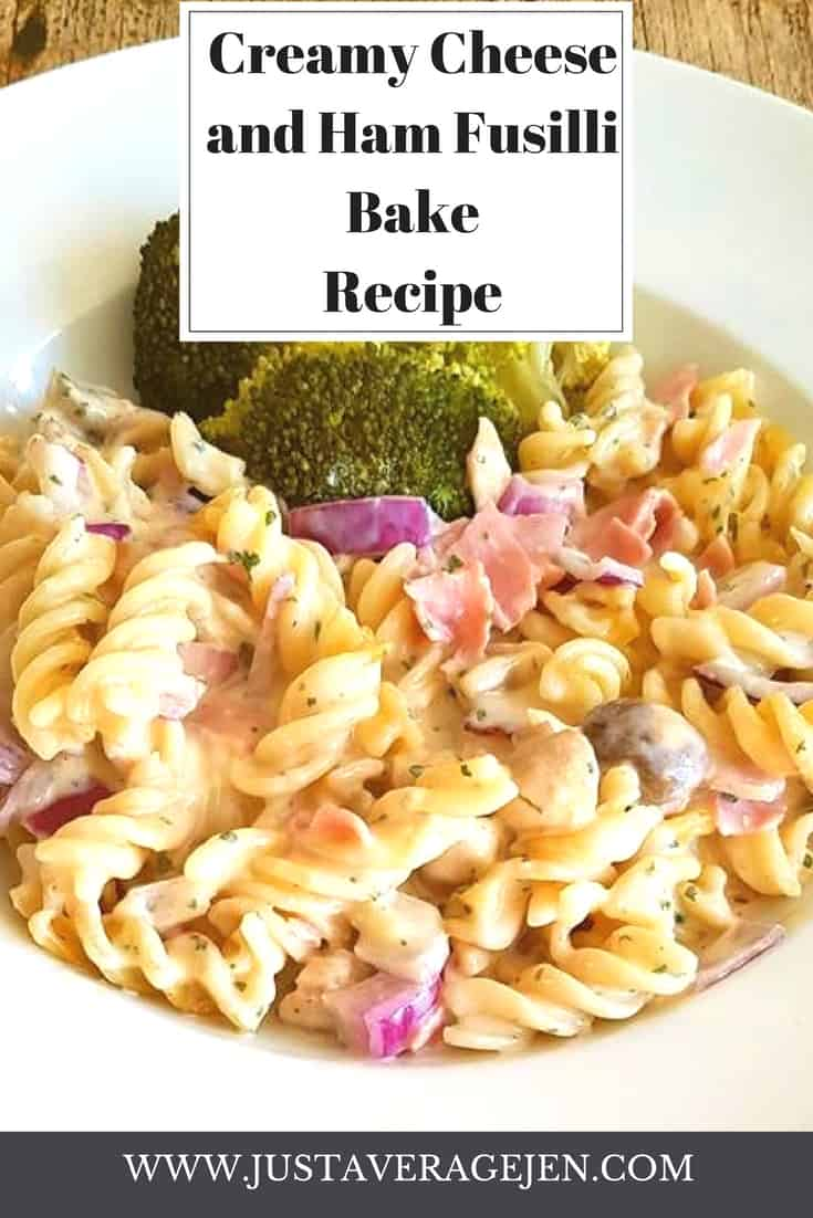 A white bowl filled with a creamy pasta with chunks of ham and served with brocolli