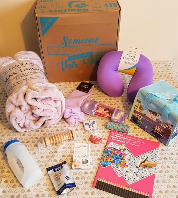 A box with the contents of the cancer care parcel spread on a table with a cream tablecloth covered in hearts.
