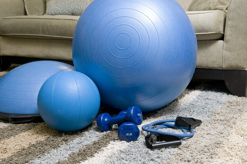 blue gym ball, two smaller ballsm two small dumbells and something unknown all on a rug infront of a sofa