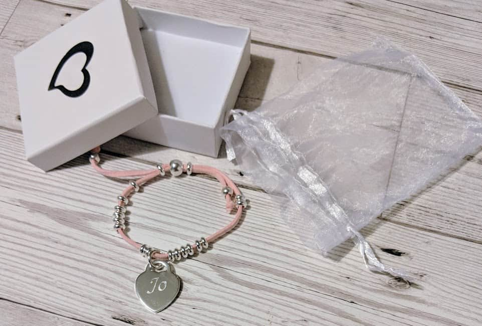 bracelet with a pale pink cord, silver coloured beads and a silver coloured heart with the name Jo engraved on it.