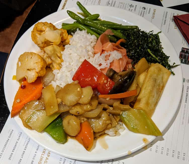 plate of boiled rice, spring roll, tenderstem broccoli and water chestnuts and veg in a soy sauce type sauce