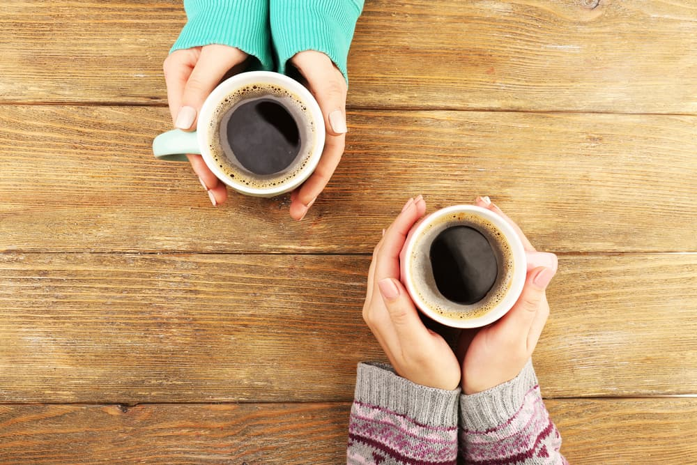 to sets of arms in jumpers holding coffee cups on a wooden table