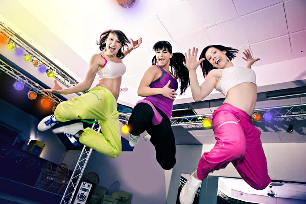 three women jumping and smiling in exercise clothing