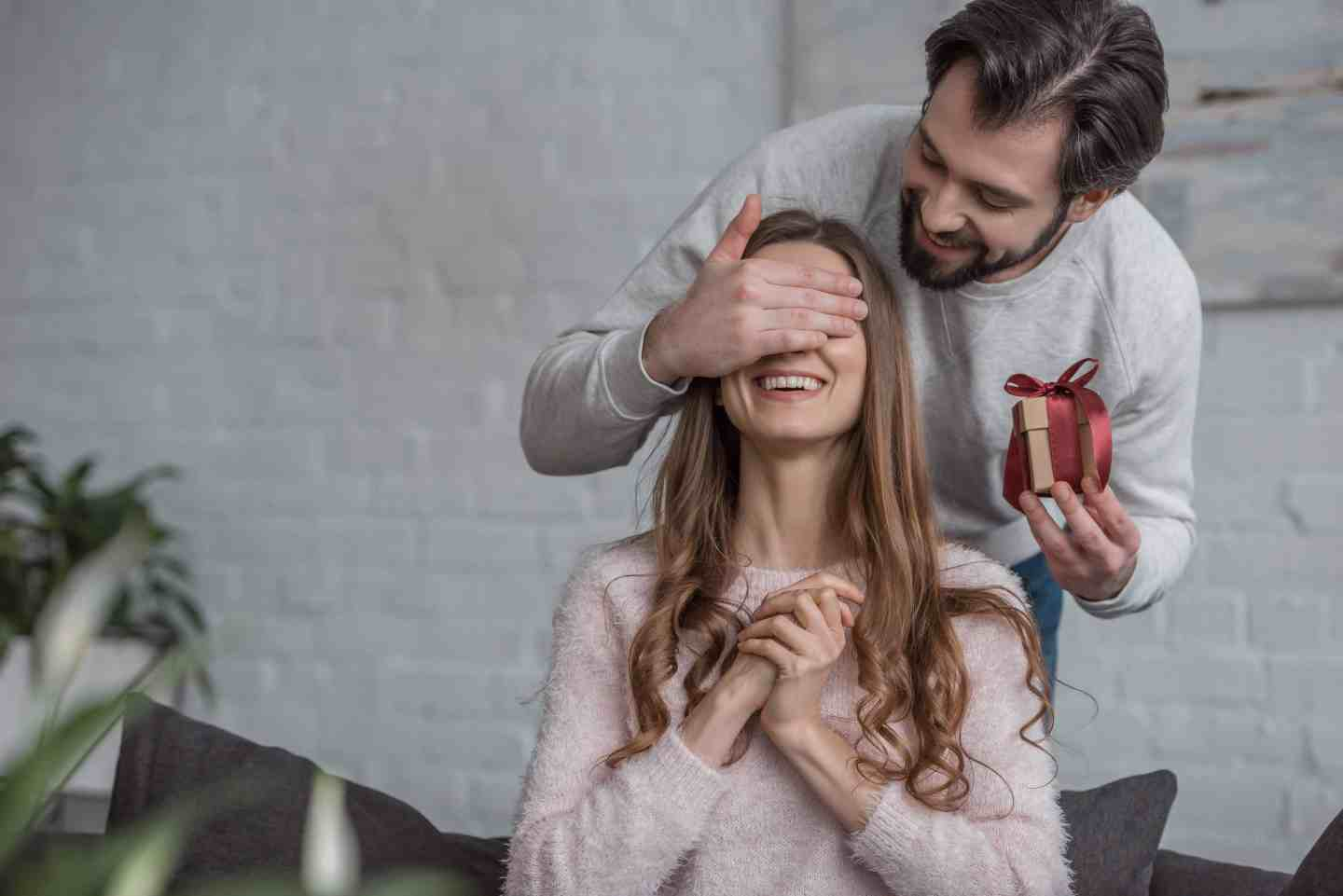 man giving a woman a gift with her eyes covered