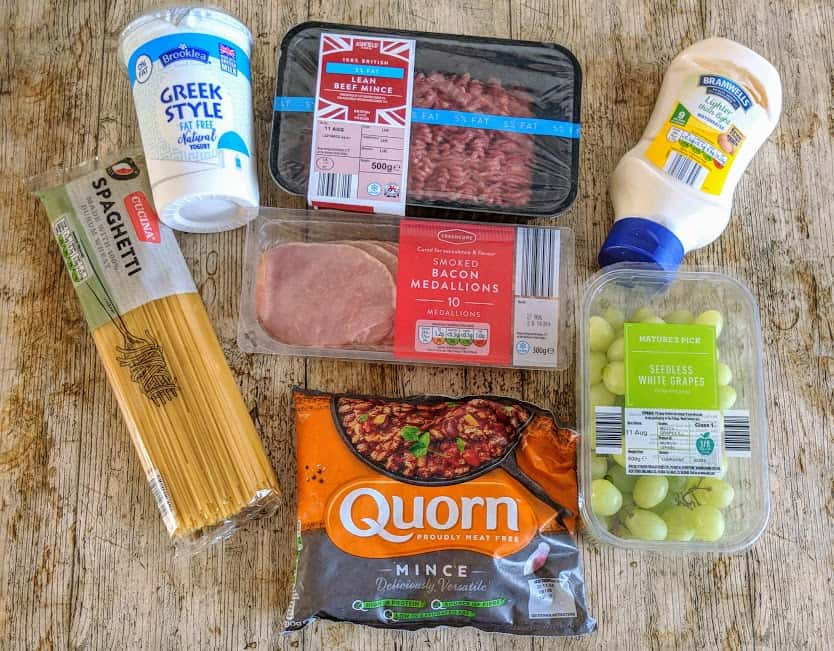 mince, spaghetti, greek yoghurt, mayonnaise, grapes, quorn mince and bacon medallions on a wooden table