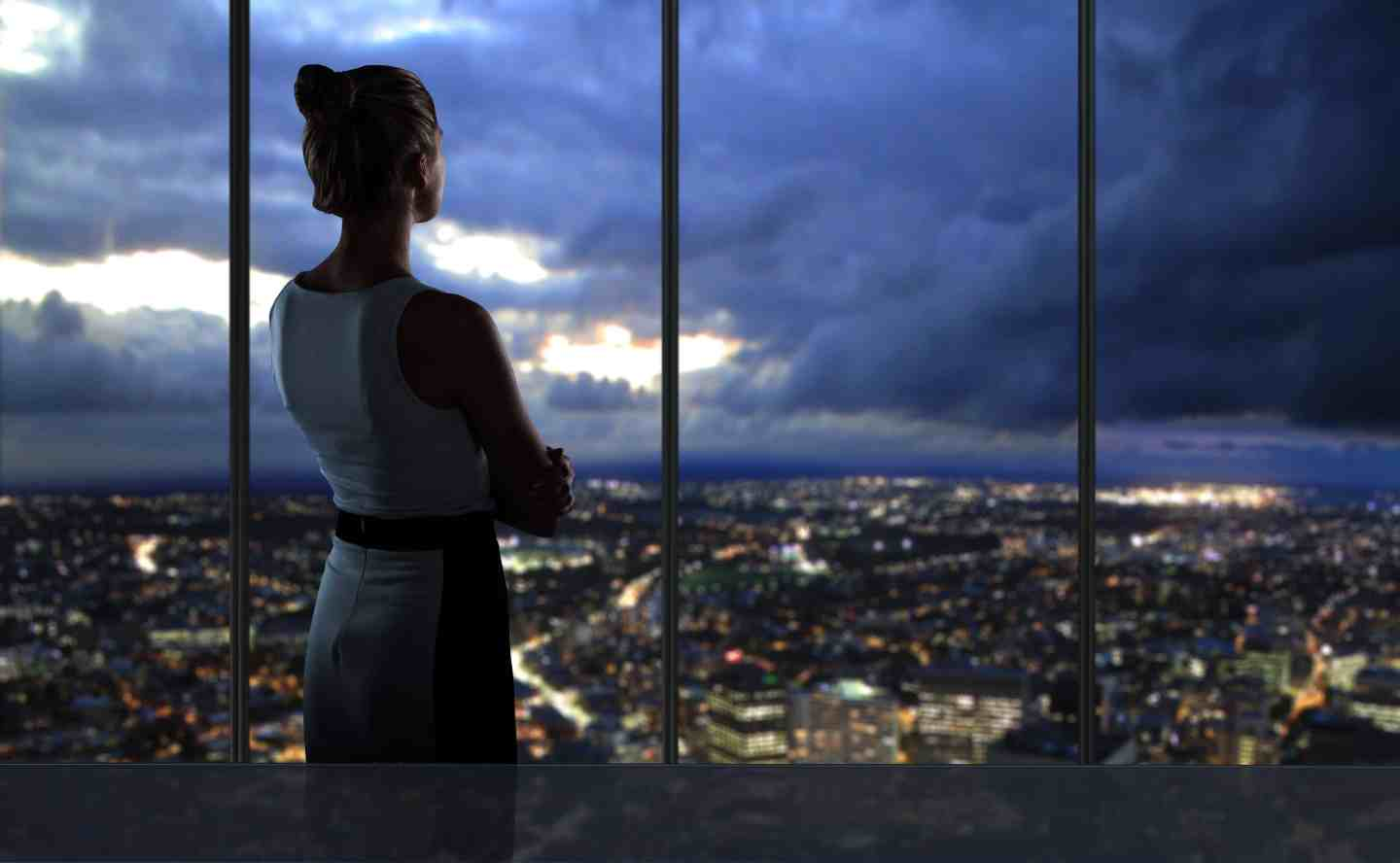 woman looking over city at night
