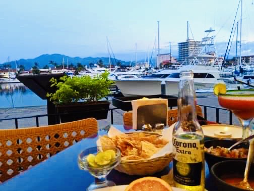 A small table with a margarita, corona, and nachos on. Past the table is a boat on the water.