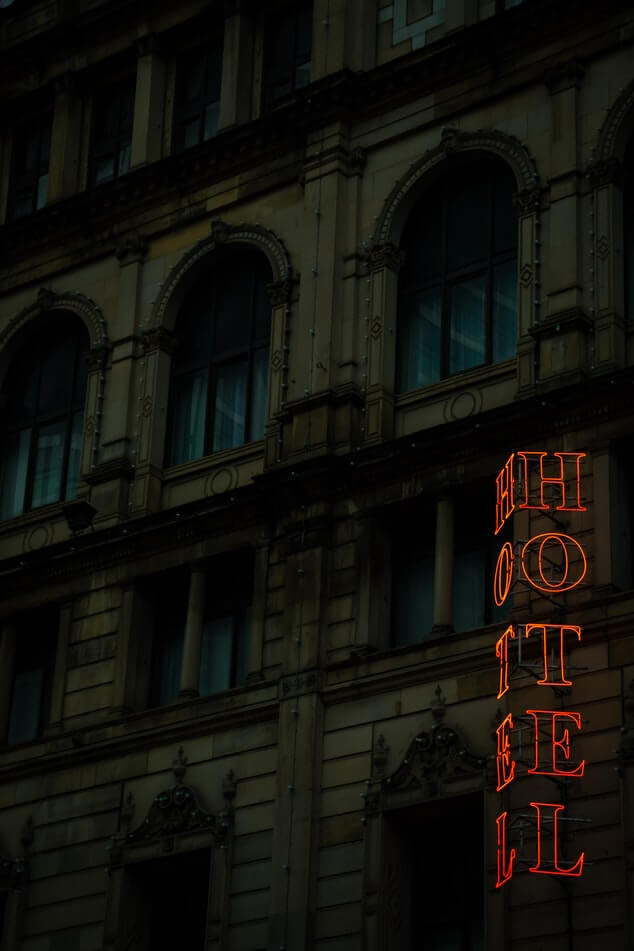 A darkened hotel with the word Hotel in neon red on a sign