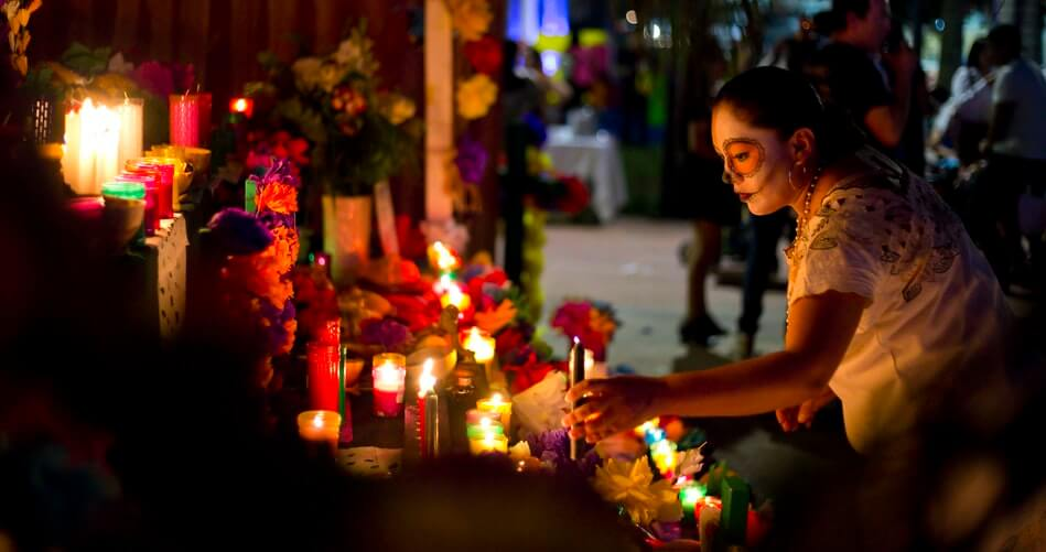 A woman placing a flower on a table laid out and decorated for Dia de Los Muertos