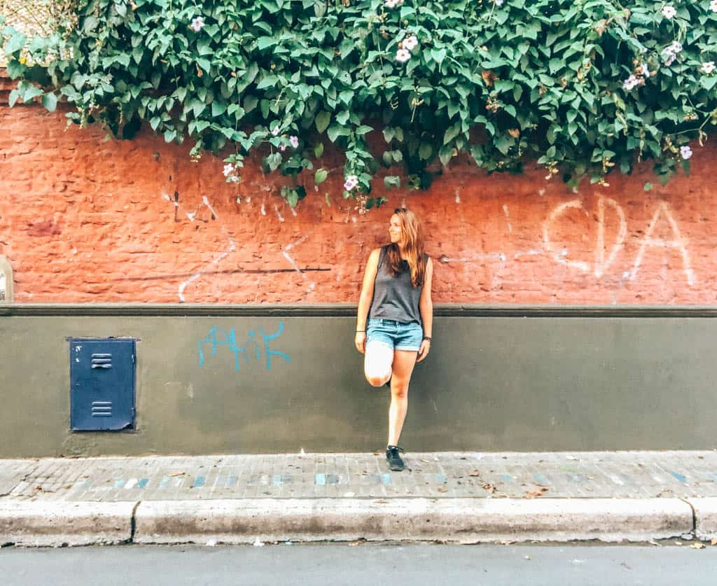Girl standing in front of a brick wall