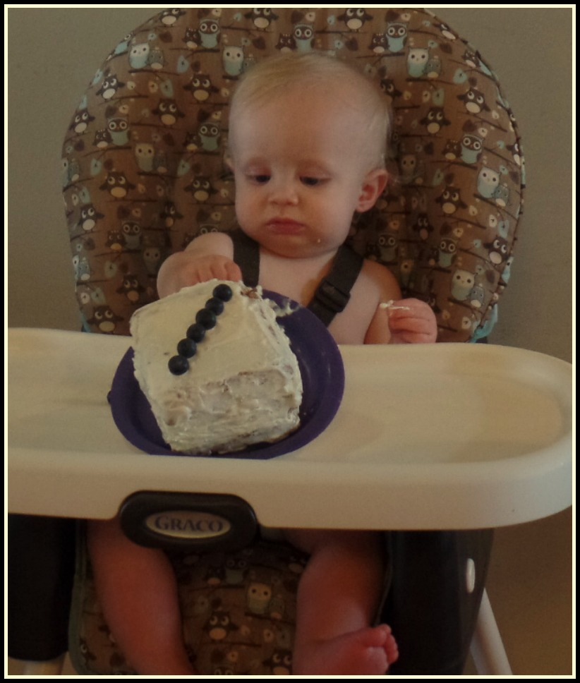 Baby with healthy smash cake, uncertain expression