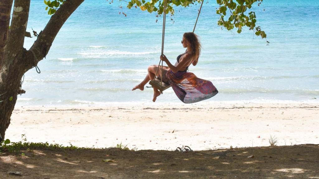 girl on tree swing on the beach koh yao noi thailand