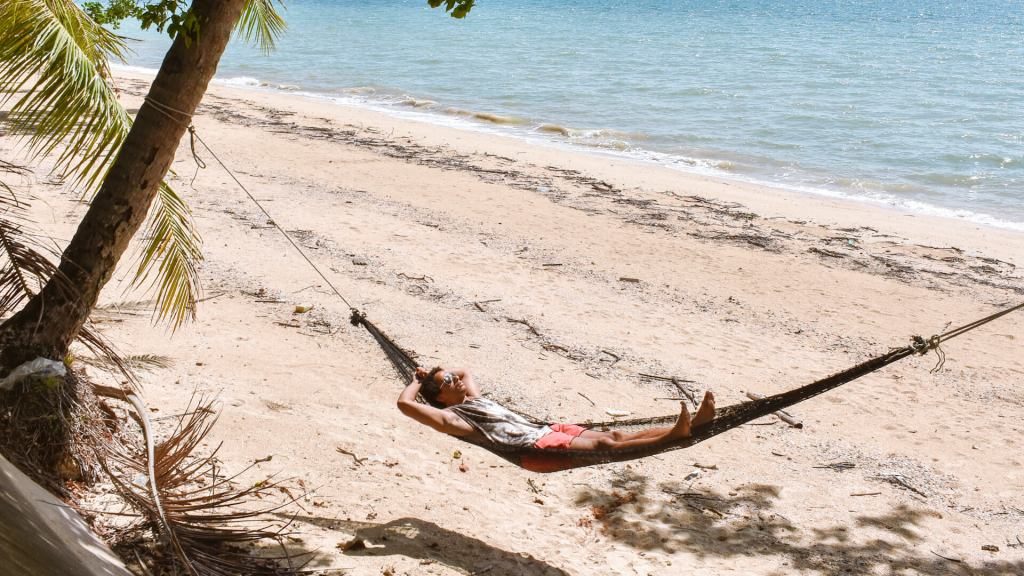 man chilling in hammock on the beach koh yao noi thailand
