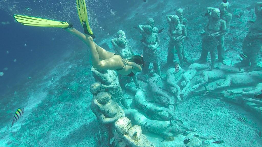 Girl swimming underwater statues Gili Meno Indonesia