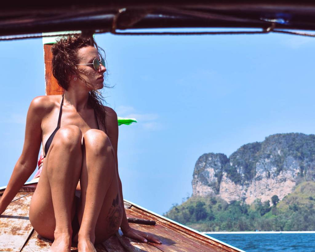 Women sunbathing on a long tail boat in Thailand, 4 Island Tour.